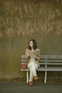 ベンチに座り本を読む女性の写真素材 [FYI04556044]