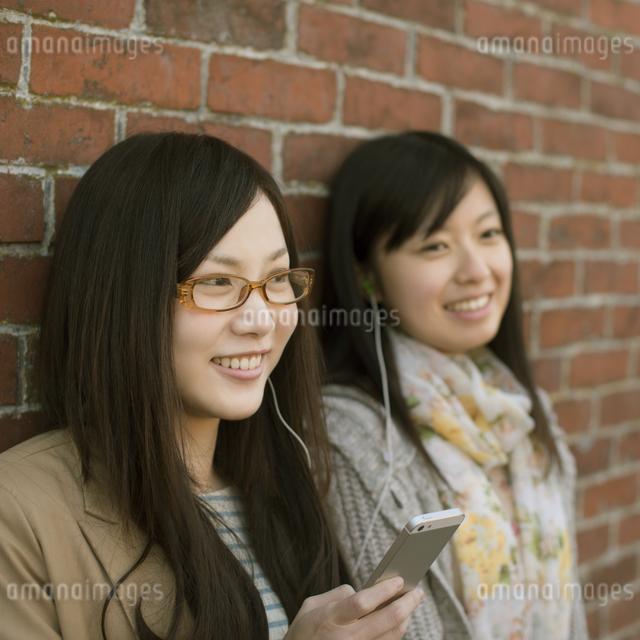 スマートフォンで音楽を聴く2人の女性の写真素材 [FYI04556056]
