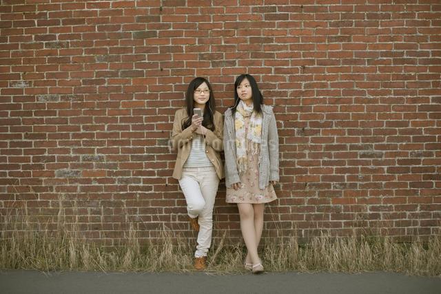 スマートフォンで音楽を聴く2人の女性の写真素材 [FYI04556061]