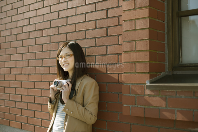 カメラを持ち微笑む女性の写真素材 [FYI04556147]