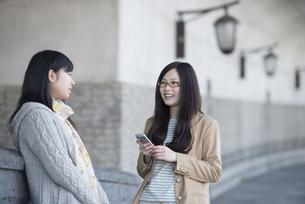 スマートフォンを持ち談笑をする2人の女性の写真素材 [FYI04556153]