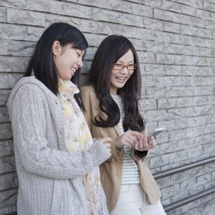 スマートフォンの画面を見る2人の女性の写真素材 [FYI04556156]