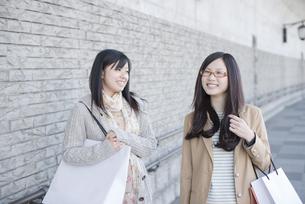 ショッピングバッグを持ち談笑をする2人の女性の写真素材 [FYI04556168]