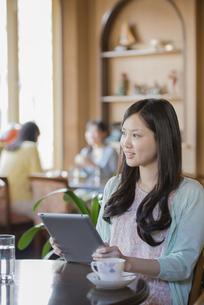 タブレットPCを持ち微笑む女性の写真素材 [FYI04556240]