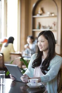 タブレットPCを持ち微笑む女性の写真素材 [FYI04556242]