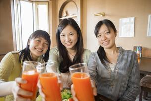 野菜ジュースを持ち微笑む3人の女性の写真素材 [FYI04556249]