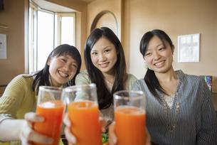 野菜ジュースを持ち微笑む3人の女性の写真素材 [FYI04556251]