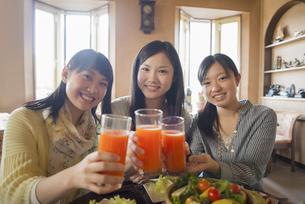 野菜ジュースを持ち微笑む3人の女性の写真素材 [FYI04556255]