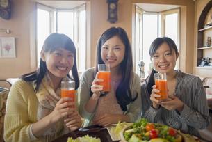 野菜ジュースを持ち微笑む3人の女性の写真素材 [FYI04556256]