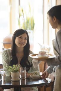 カフェで店員と談笑をする女性の写真素材 [FYI04556270]