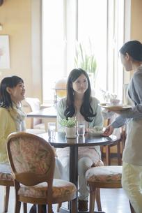 カフェで店員と談笑をする女性の写真素材 [FYI04556271]