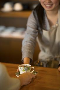 カフェでコーヒーを差し出す手元の写真素材 [FYI04556273]