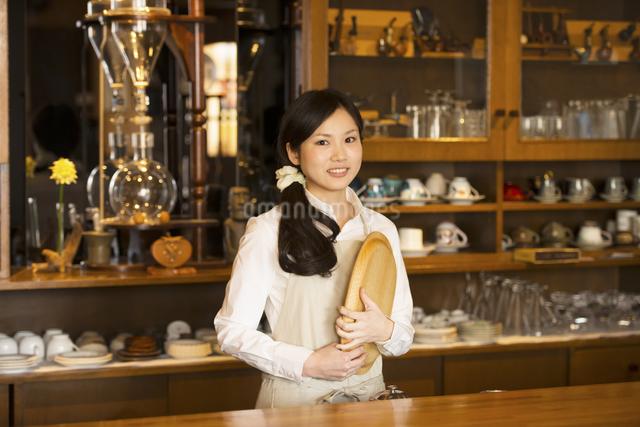 お盆を持ち微笑むカフェの店員の写真素材 [FYI04556292]