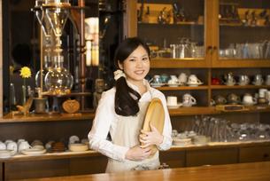お盆を持ち微笑むカフェの店員の写真素材 [FYI04556293]