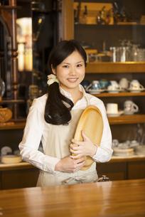 お盆を持ち微笑むカフェの店員の写真素材 [FYI04556294]