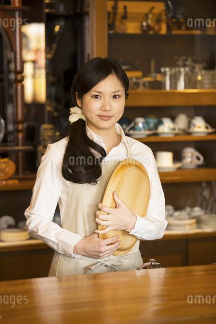 お盆を持ち微笑むカフェの店員の写真素材 [FYI04556295]