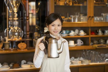ポットを持ち微笑むカフェの店員の写真素材 [FYI04556298]