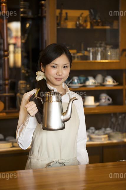 ポットを持ち微笑むカフェの店員の写真素材 [FYI04556299]