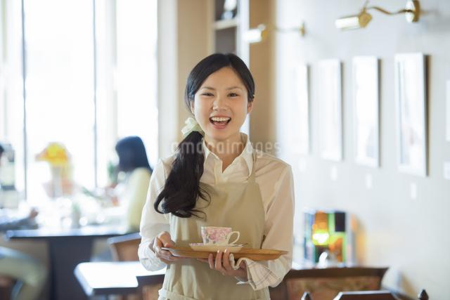 お盆を持ち微笑むカフェの店員の写真素材 [FYI04556300]