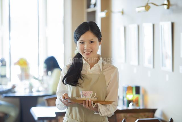お盆を持ち微笑むカフェの店員の写真素材 [FYI04556301]