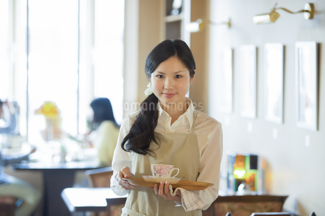 お盆を持ち微笑むカフェの店員の写真素材 [FYI04556302]