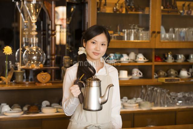 ポットを持ち微笑むカフェの店員の写真素材 [FYI04556303]