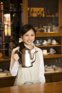 ポットを持ち微笑むカフェの店員の写真素材 [FYI04556304]