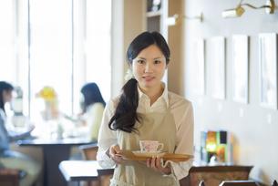 お盆を持ち微笑むカフェの店員の写真素材 [FYI04556305]