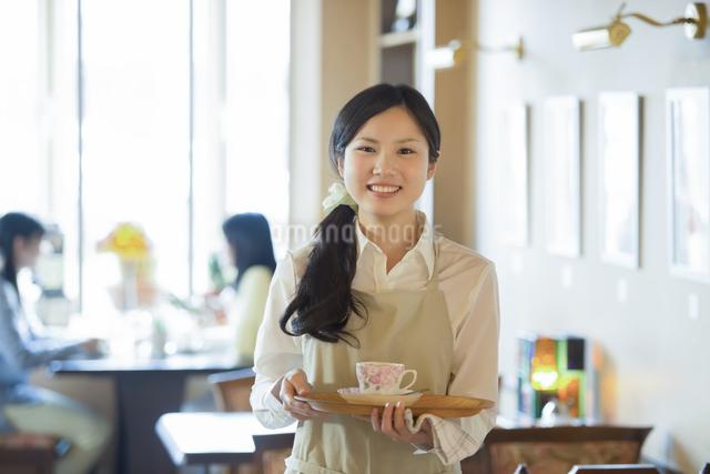 お盆を持ち微笑むカフェの店員の写真素材 [FYI04556306]