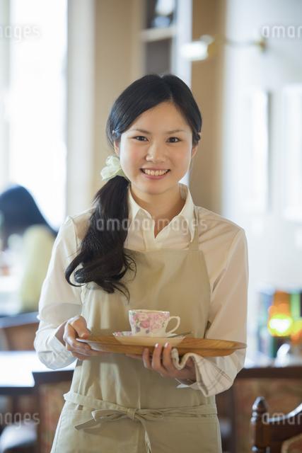 お盆を持ち微笑むカフェの店員の写真素材 [FYI04556307]