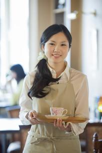 お盆を持ち微笑むカフェの店員の写真素材 [FYI04556308]