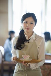お盆を持ち微笑むカフェの店員の写真素材 [FYI04556309]