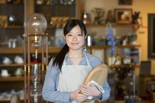 お盆を持ち微笑むカフェの店員の写真素材 [FYI04556310]