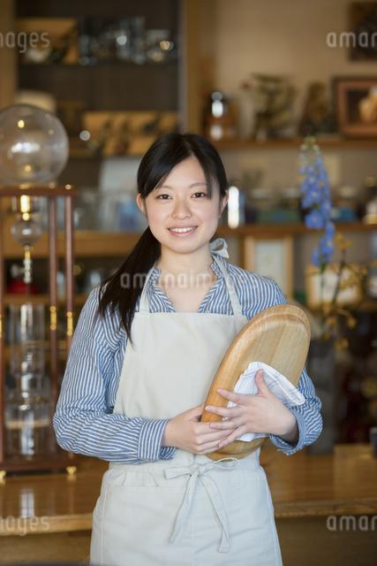 お盆を持ち微笑むカフェの店員の写真素材 [FYI04556311]