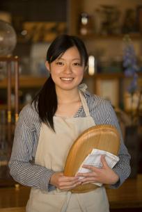 お盆を持ち微笑むカフェの店員の写真素材 [FYI04556312]