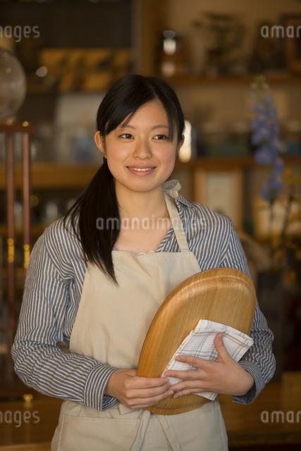 お盆を持ち微笑むカフェの店員の写真素材 [FYI04556313]