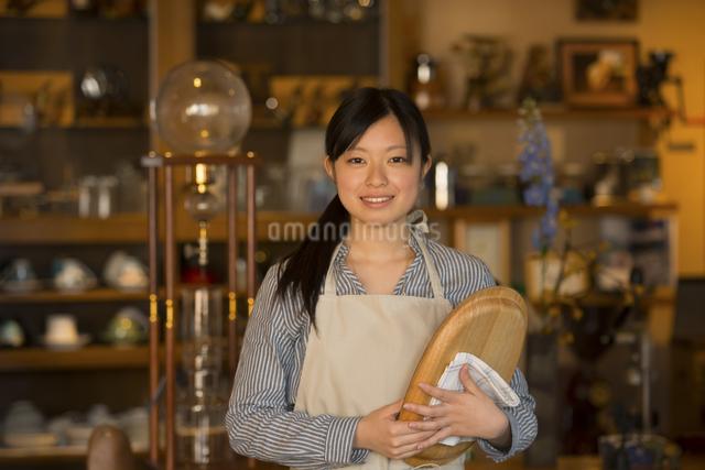 お盆を持ち微笑むカフェの店員の写真素材 [FYI04556314]