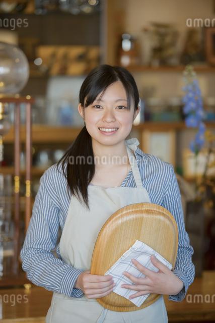 お盆を持ち微笑むカフェの店員の写真素材 [FYI04556315]
