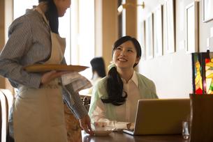 カフェの店員と談笑をする女性の写真素材 [FYI04556316]