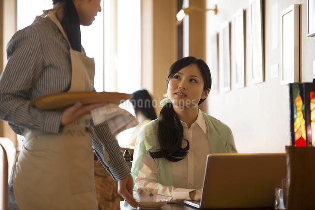 カフェの店員と談笑をする女性の写真素材 [FYI04556317]