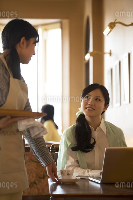 カフェの店員と談笑をする女性の写真素材 [FYI04556318]