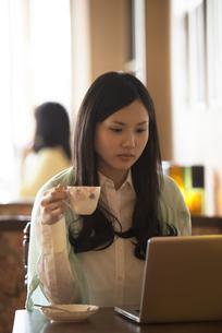 ティーカップを持ちパソコンの画面を見る女性の写真素材 [FYI04556326]