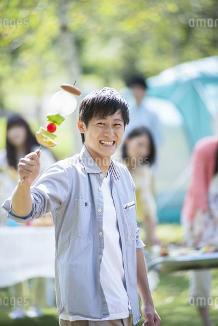 BBQの串を持ち微笑む大学生の写真素材 [FYI04556337]