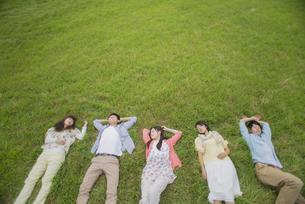 草原に寝転ぶ大学生の写真素材 [FYI04556384]