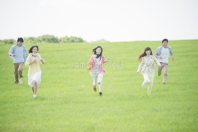 草原を走る大学生の写真素材 [FYI04556412]