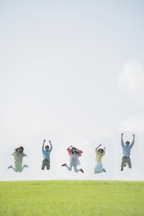 草原でジャンプをする大学生の写真素材 [FYI04556449]