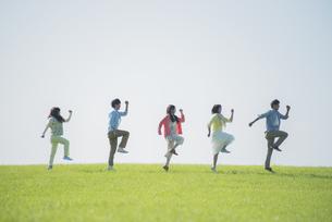 草原ではしゃぐ大学生の写真素材 [FYI04556459]