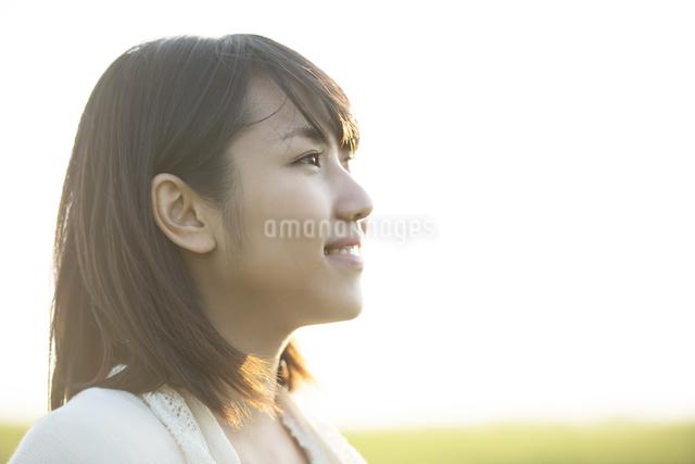 草原で微笑む女性の横顔の写真素材 [FYI04556470]
