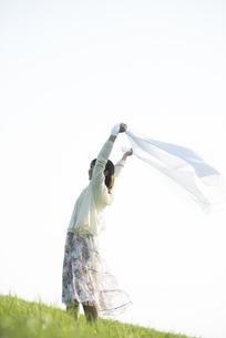 草原で布を持ち微笑む女性の写真素材 [FYI04556495]
