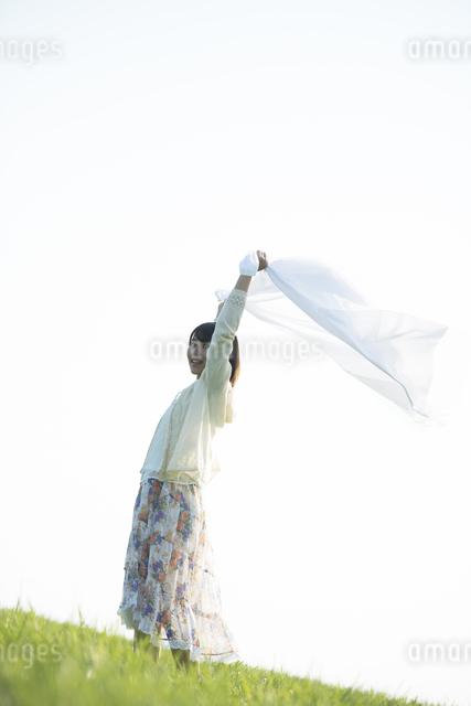 草原で布を持ち微笑む女性の写真素材 [FYI04556497]